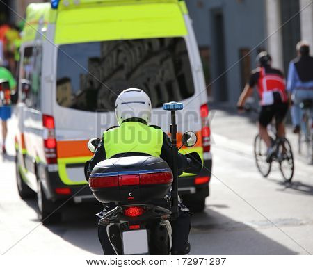 motorcycle police while escorting an ambulance in the traffic in the city