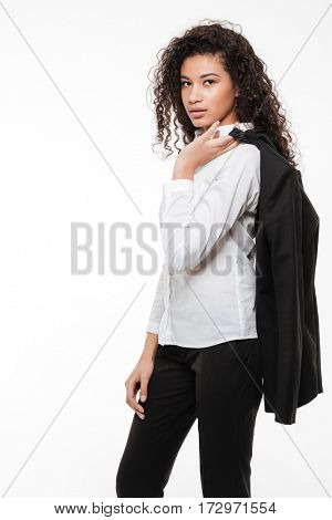Confident african young businesswoman standing with jacket on shoulder over white background