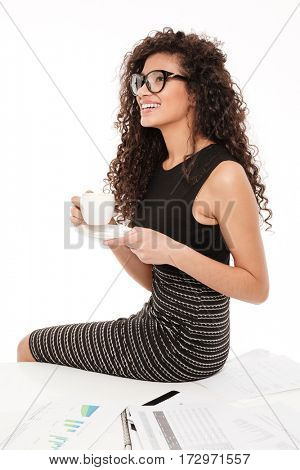 Image of pretty young curly african lady sitting over white background on table with documents drinking coffee.