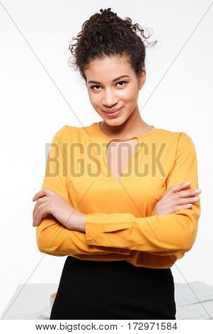 Photo of amazing young curly african lady standing over white background. Looking at camera.