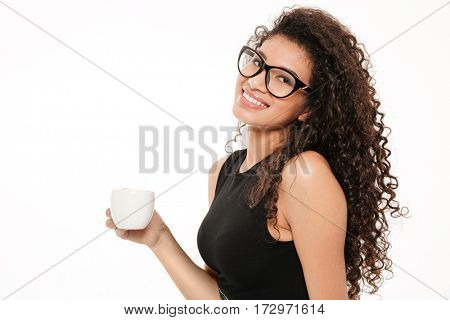 Picture of incredible young curly african lady standing over white background drinking coffee.