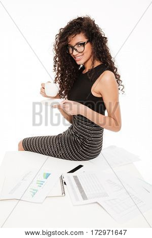 Photo of gorgeous young curly african lady sitting over white background on table with documents. Drinking coffee.