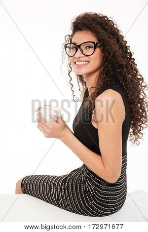 Image of gorgeous young curly african lady sitting over white background drinking coffee.