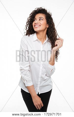 Image of happy young curly african woman standing and posing over white background. Looking aside.