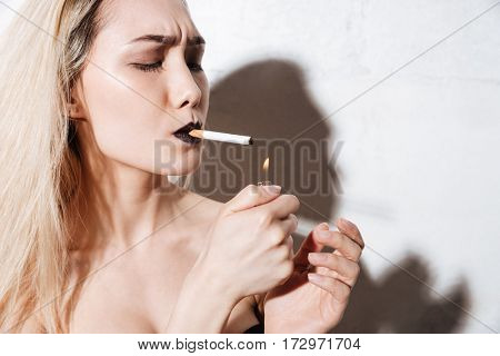 Close-up portrait of Cool Hipster woman scorch the cigarette. Isolated gray background