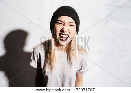 Angry irritated young woman in black hat standing and screaming over white background