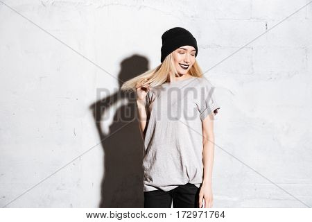 Happy pretty young woman in hat with gothic makeup standing and smiling over white background