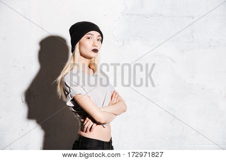 Confident young woman in hat with black lipstick standing with arms crossed over white background