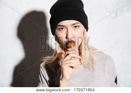 Close up portrait of Cool Hipster woman in black hat which licking the lollipop and looking at camera