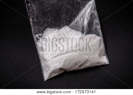Cocaine in plastic packet on black background, macro closeup photo. Portion of drugs