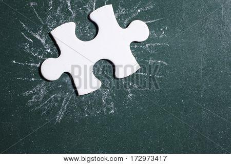 single piece of puzzle on the blackboard