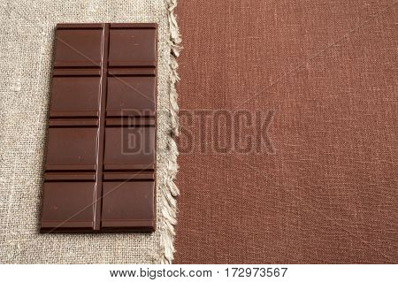 Chocolate bar on a natural linen in two colors to match the chocolate with copy space