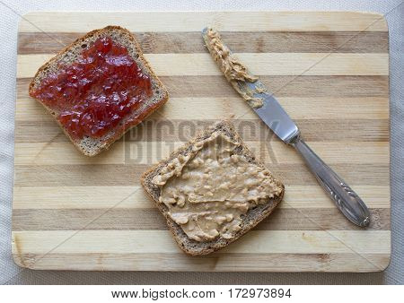 One sandwich with jam and other with peanut butter on wooden chopping block
