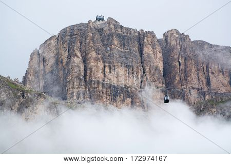 Sass Pordoi mountain massif hidden in clouds with cable car leading on top Dolomites Italy
