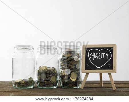 Blackboard with words charity and three saving jars from little coins ,half to full.