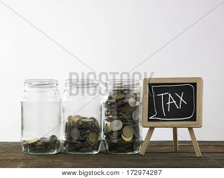 Blackboard with words tax and three saving jars from little coins ,half to full.