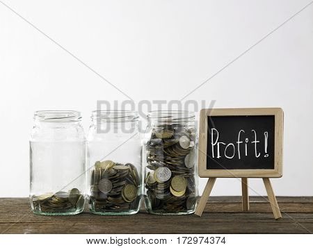 Blackboard with words profit and three saving jars from little coins ,half to full.