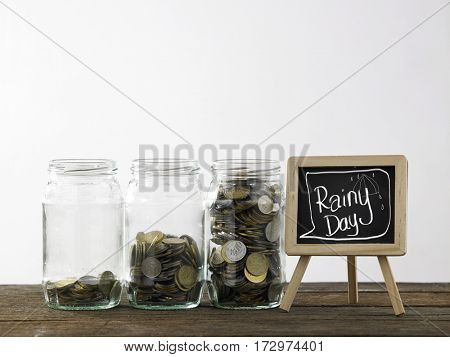 Blackboard with words rainy day and three saving jars from little coins ,half to full.
