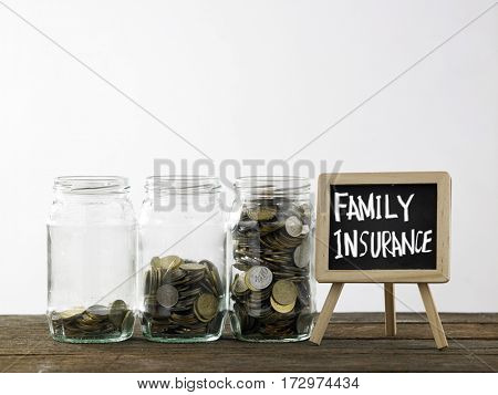Blackboard with words family insurance and three saving jars from little coins ,half to full.