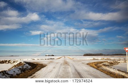 Four way gravel roads disecting agriculture farmland dotted with forests of trees in a morning sunrise winter landscape