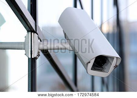 white security cctv camera on glass facade