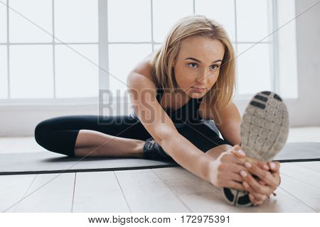 Attractive slim female doing stretching exercises on black mat in modern bright fitness center. Hardworking beautiful girl working with her left leg stretching it with both arms. Close up