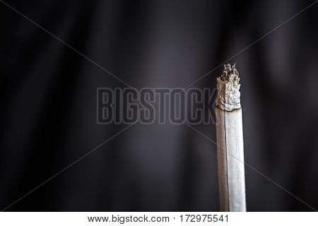 Thin smoldering cigarette on a dark background. Macro photo. Copy space for text