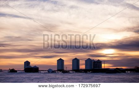 Old farm sheds and granaries with tall modern steel grain bins in an abandoned farm yard in a winter sunset