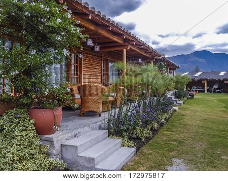 Touristic rustic style wood house with garden decoration and mountains and cloudy sky at background at San Pablo lake Imbabura Ecuador