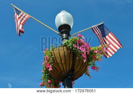 A street lamp post decorated with United State National flags and flower pot in Georgetown district in Washington DC USA