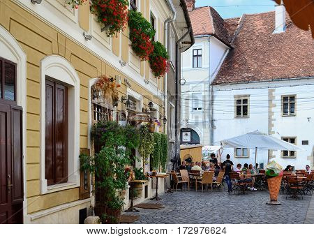 CLUJ-NAPOCA ROMANIA - AUGUST 4 2012: Tourists visit and have lunch at outdoor restaurant cafe outdoors in the old historic town center in front of the Matthias Corvinus Memorial House.
