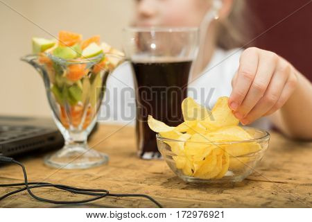 Girl eats potato chips and fruit salad in front of laptop. Unhealthy eating in front of computer.