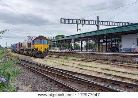 Didcot, UK. 24th July 2016. DB Schenker Class 66 locomotive (66124) is stationary in the sidings at Didcot Parkway station with a rake of container wagons behind.