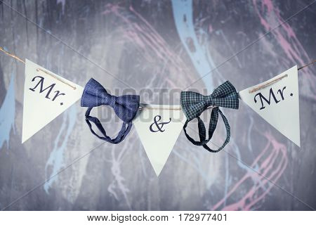 Paper garland and bow ties on grey textured wall background