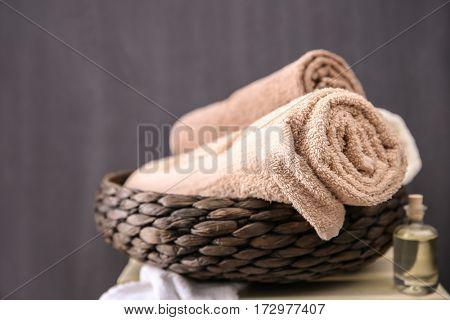 Spa towels in wicker basket on dark background