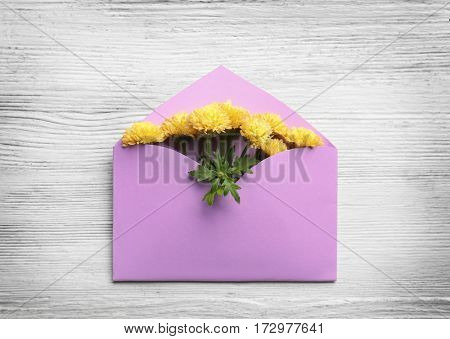 Decorative envelope with chrysanthemum flowers on white wooden background