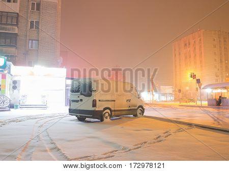 Rear lights of car on parking in dark foggy winter evening