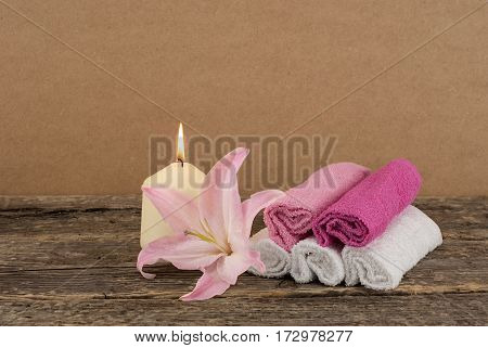 Beautiful composition with candle, pink lily flower and spa towels on wooden background, zen and wellness concept
