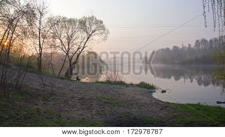 Man catch the fish at foggy river in sunrise