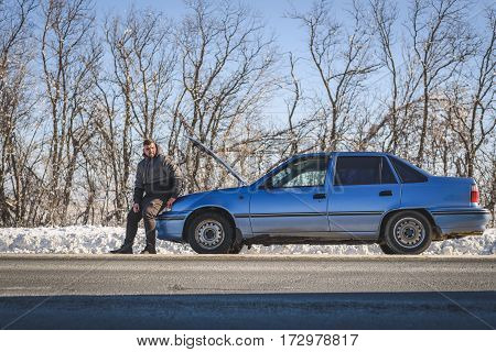 Boy Sitting On The Hood Of Car Catches