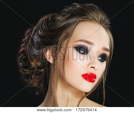 Gorgeous Young Woman face portrait. Beauty Model Girl with bright eyebrows, perfect make-up, red lips, hairstyle, looking away.Sensual lady makeup for party. Isolated on black background. Smokey eyes. Studio