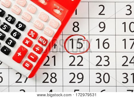 Red calculator on marked calendar, closeup
