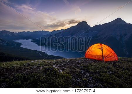 Glowing tent set up on a ridge for camping in the Rocky mountains