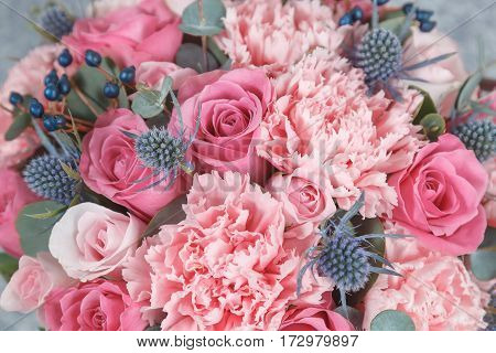 Pink roses, carnations and blue thistle flowers background