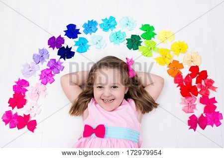 Little girl in pink pastel dress choosing colorful hair accessories. Bow and ribbon for kids. Hair style and accessory for children. Choice of bows. Rainbow ribbons for girls. View from above on white