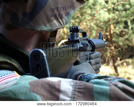 Airsoft player as American soldier take aim