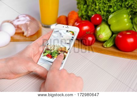 Woman with phone and ingredients on kitchen table