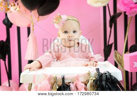 Cute little birthday girl sitting on high chair in room decorated for party