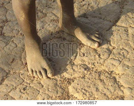 Person standing on drought-affected cracked soil in Burkina Faso, West Africa