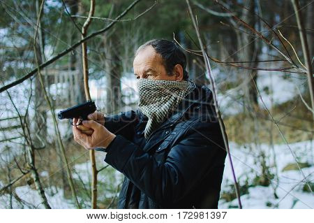 An elderly man with a gun in the woods in early spring. Man dressed in a black jacket. The face of unknown covered by a scarf. He holds the gun in both hands and aiming into the distance